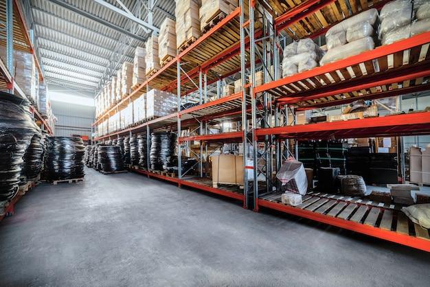 Magazijn industriële goederen. grote lange rekken. kartonnen dozen en opgerolde plastic buis. het beeld versterken.