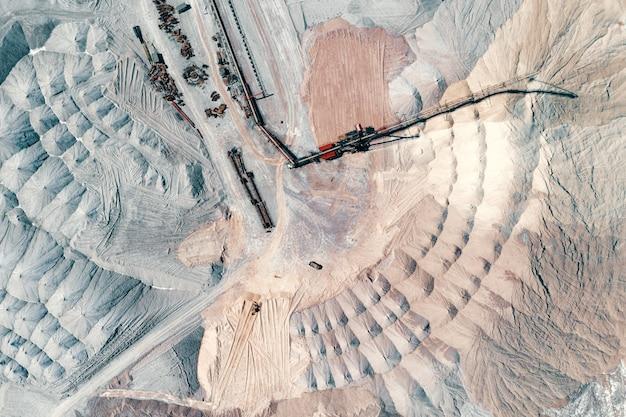 Magazijn van ongebruikte rots. erts wordt opgeslagen in enorme terpen. een systeem van lange transportbanden en spreiders.