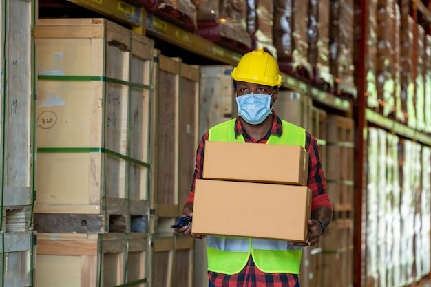 Magazijnarbeiders die een beschermend masker dragen dat bij pakhuis werkt, werken zij in de industrie die fabriek produceren.