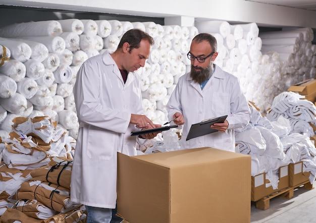 Magazijnbegeleider en manager mannen met textiel
