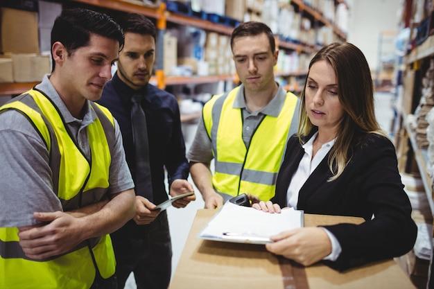 Magazijnbeheerder en werknemers praten in het magazijn