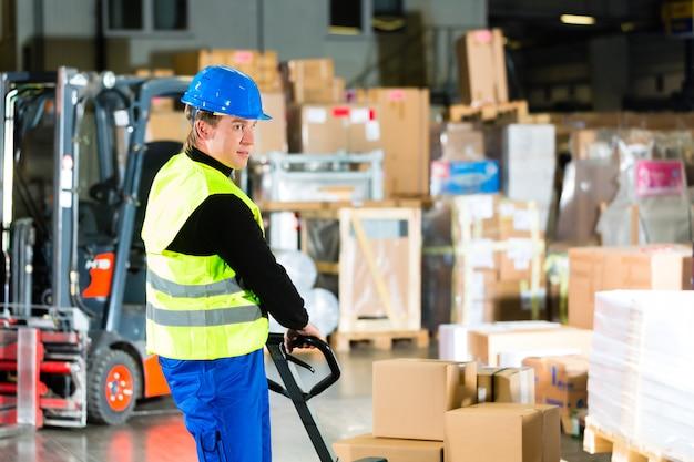Magazijnier in beschermend vest trekt een verhuizer met pakketten en dozen bij magazijn van expeditiebedrijf een vorkheftruck
