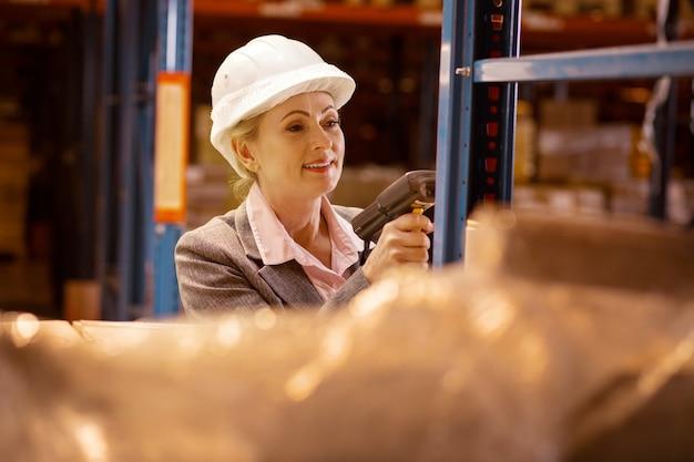 Magazijninventaris. blije opgetogen vrouw die goederen scant terwijl ze de inventaris van het pakhuis controleert
