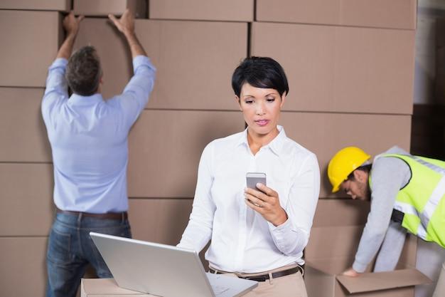 Magazijnmanager die laptop en texting op telefoon met behulp van