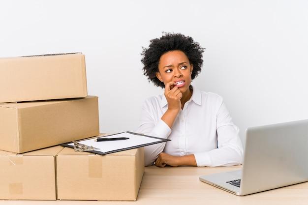 Magazijnmanager zit leveringen controleren met laptop ontspannen denken aan iets kijken naar een kopie ruimte.