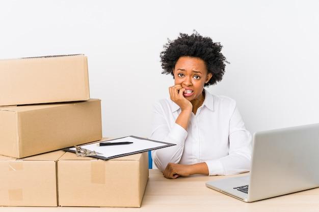 Magazijnmanager zit leveringen te controleren met bijtende nagels van de laptop, zenuwachtig en erg angstig.