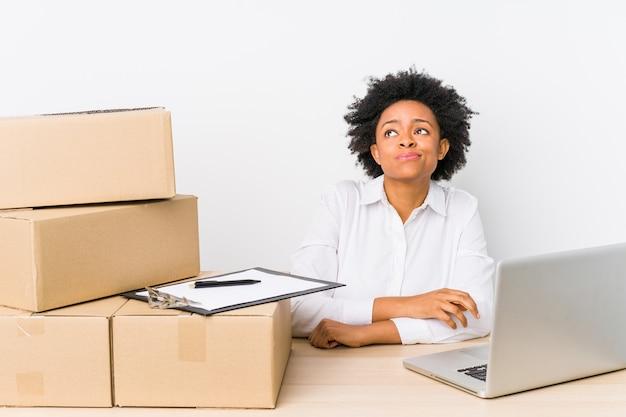Magazijnmanager zit leveringen te controleren met laptop en droomt van het bereiken van doelen en doelen