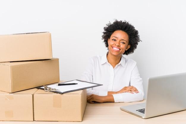Magazijnmanager zitten leveringen controleren met laptop blij, lachend en opgewekt.