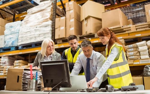 Magazijnmanagers en arbeider die aan laptop werken