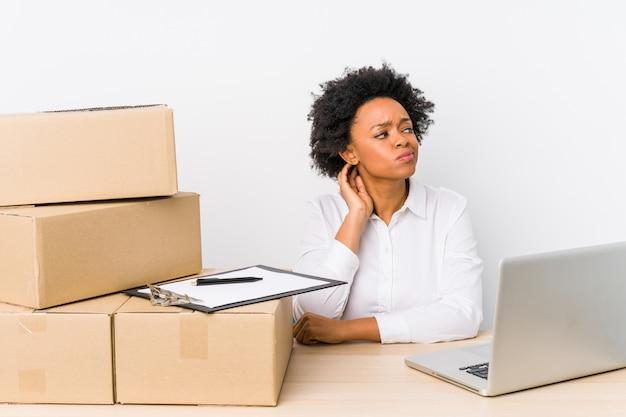 Magazijnmanagerzitting die leveringen controleren met laptop die het achterhoofd raakt, denkt en een keuze maakt.