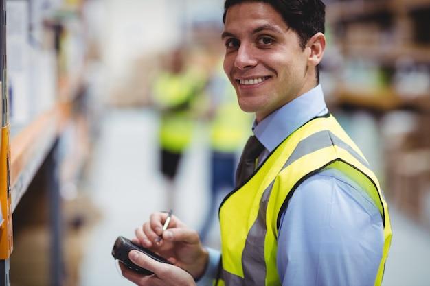 Magazijnmedewerker die handscanner in magazijn met behulp van