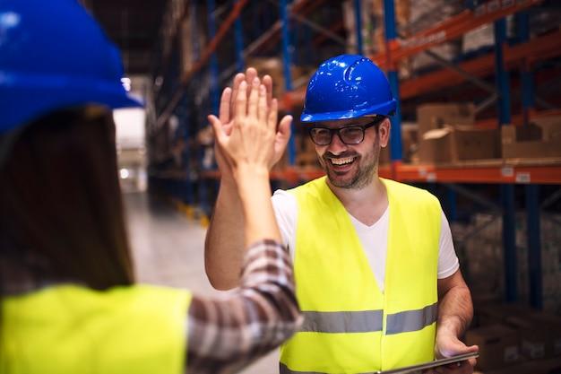 Magazijnmedewerker die high five geeft aan zijn vriendcollega