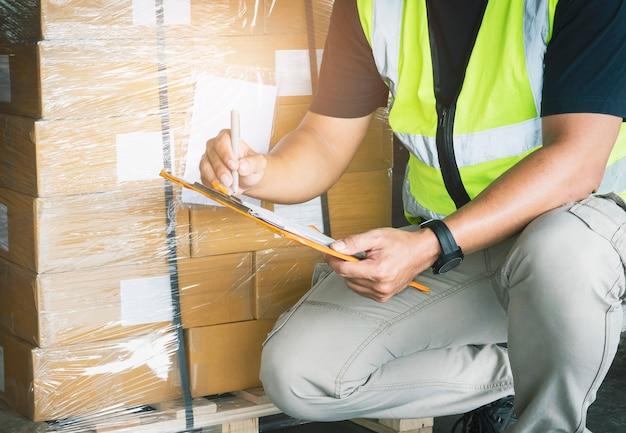 Magazijnmedewerker die op papieren klembord schrijft, zijn verzenddozen controleren