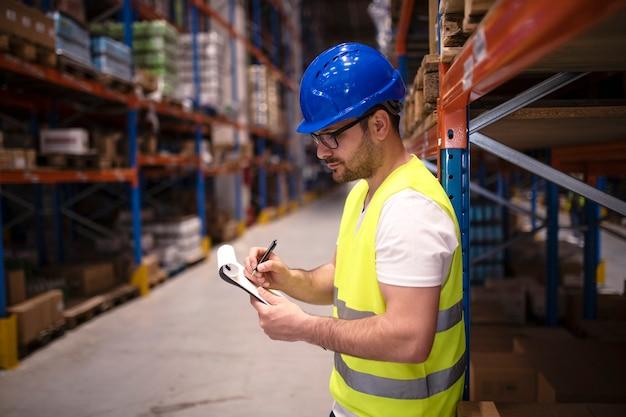 Magazijnmedewerker die voorraad in groot distributiecentrum controleert