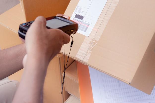 Magazijnmedewerker houdt barcode scanner met scannen op label een pakket box voor het verzenden naar de klant.