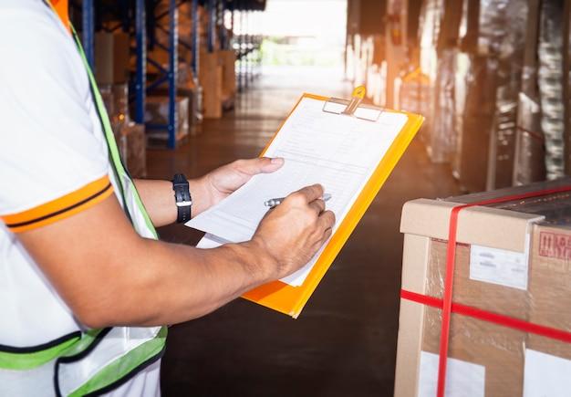 Magazijnmedewerker klembord houden zijn bezig voorraadbeheer vrachtdozen. voorraad controleren, vrachtverzending, magazijnopslag.