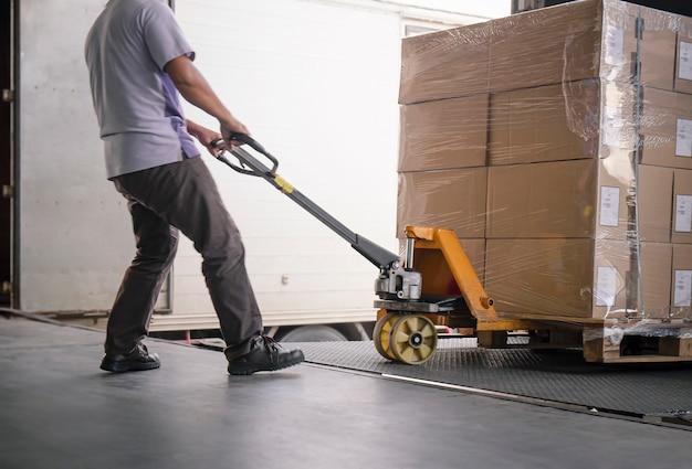 Magazijnmedewerker lossen vrachtdozen op pallet. ladingsvrachtwagen geparkeerd laden bij dokmagazijn.