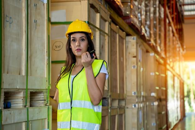 Magazijnmedewerker met handheld radio-ontvanger voor communicatie in een groot magazijn.