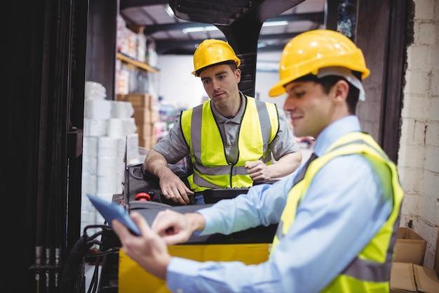 Magazijnmedewerker praten met heftruckchauffeur in magazijn