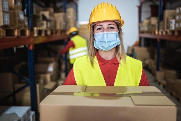 Magazijnmedewerker vrouw met leveringsdoos terwijl ze een veiligheidsmasker draagt voor coronaviruspreventie - focus op gezicht