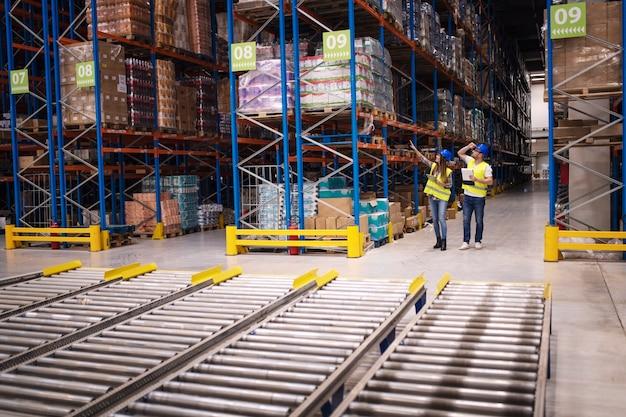 Magazijnmedewerkers controleren inventaris en goederendistributie in groot pakhuis Gratis Foto