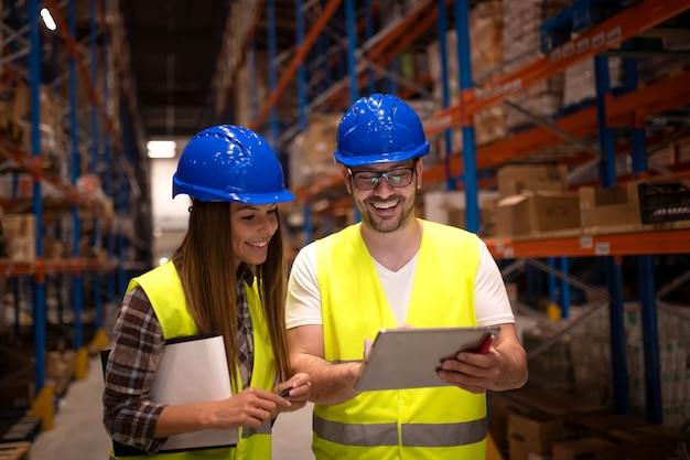 Magazijnmedewerkers die de verzendstatus op tabletcomputer controleren