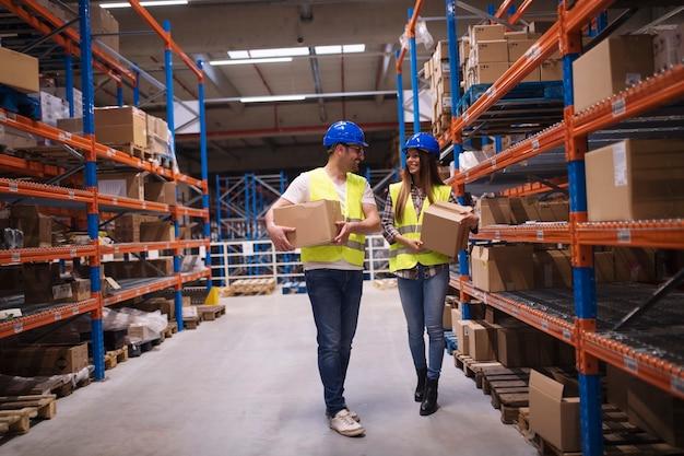 Magazijnmedewerkers die dozen in opslagruimte dragen en ze op de planken zetten