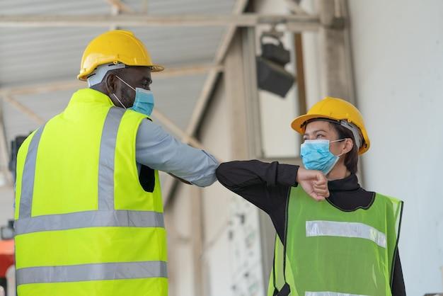 Magazijnmedewerkers die een gezichtsmasker dragen ter bescherming van de groet van het coronavirus, stoten tegen de ellebogen in de logistieke magazijnfabriek