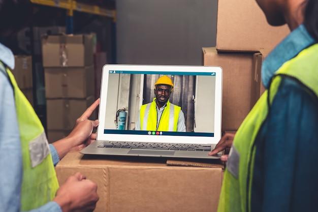 Magazijnpersoneel praten over video-oproep op computerscherm in opslagplaats