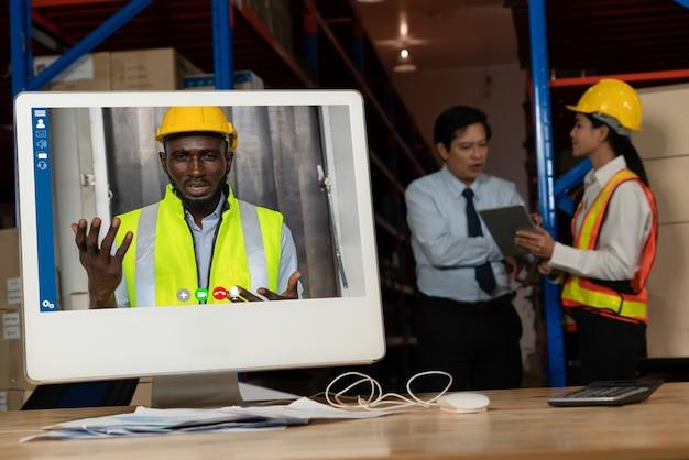 Magazijnpersoneel praten over videogesprek op computerscherm in opslagmagazijn