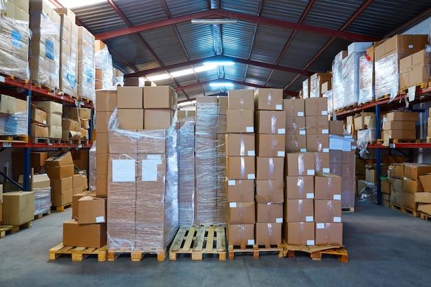Magazijnstograge met gestapelde dozen in rijen