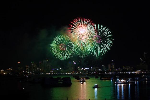 Magenta groen vuurwerk op strand en bezinningskleur op waterspiegel