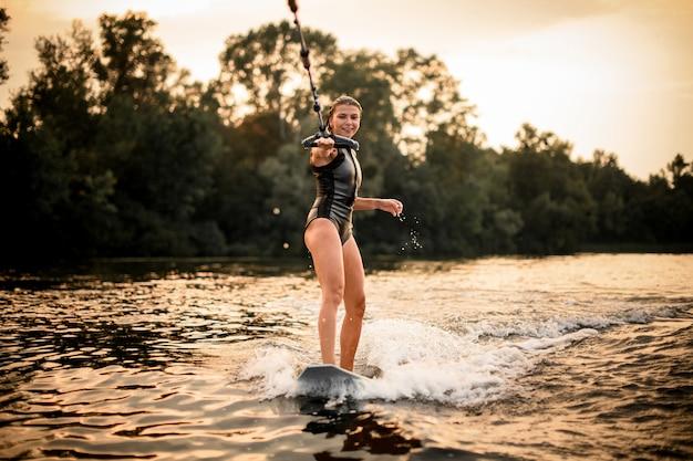 Mager meisje dat op wakeboard op de rivier in de zonsondergang berijdt die een kabel van de motorboot houdt