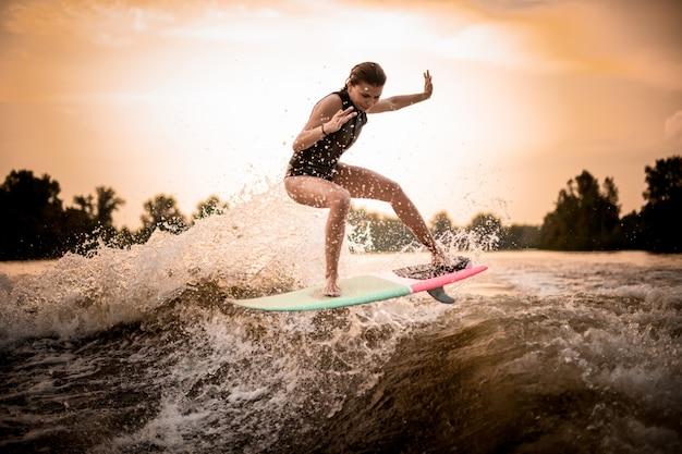 Mager meisje dat op wakeboard op de rivier op de golf in de zonsondergang springt