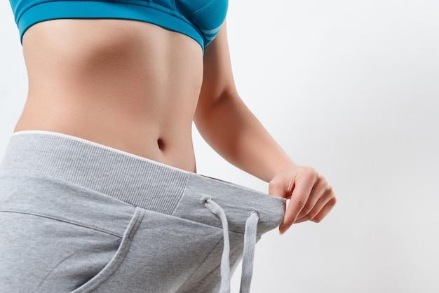 Mager meisje in grote broek - gewichtsverlies concept.