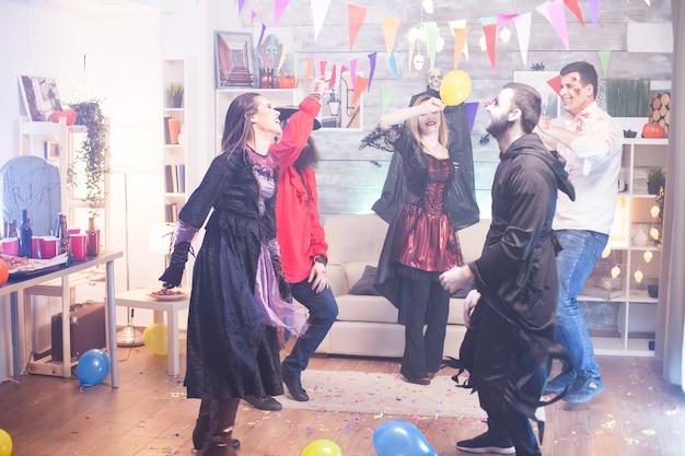 Magere hein en vrolijke heks dansen op halloween-feest. enge kostuums.