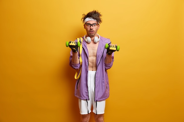 Magere man streeft naar perfect gespierd lichaam, heft halters op en staart met geschokte uitdrukking, draagt koptelefoon en sportkleding, traint in de sportschool, verrast om af te vallen, heeft zware training