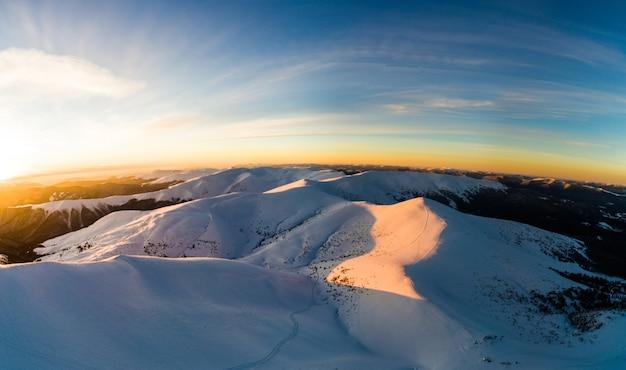 Magisch de winterpanorama van mooie besneeuwde hellingen bij een skiresort in europa op zonnig
