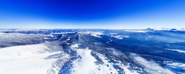 Magisch panorama van een prachtige heuvel in de bergen vallende sneeuw op de skipiste op een zonnige dag met een heldere blauwe hemel. winter toerisme concept. copyspace