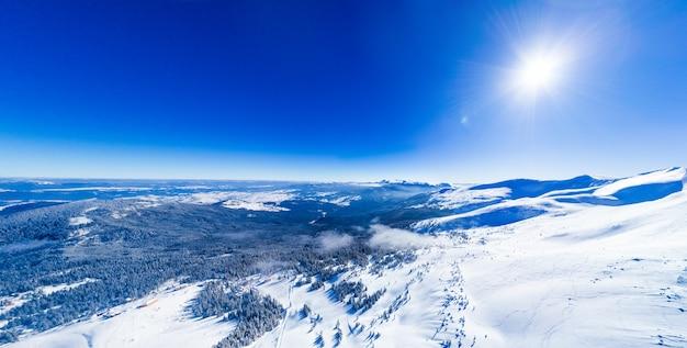 Magisch panorama van een prachtige heuvel in de bergen vallende sneeuw op de skipiste op een zonnige dag met een heldere blauwe hemel