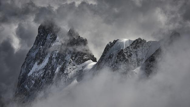 Magisch schot van een mooie besneeuwde bergtop bedekt met wolken.
