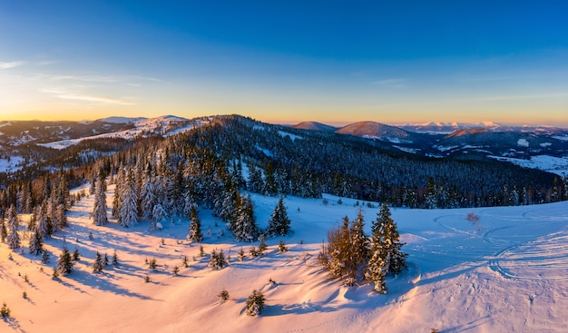 Magisch winterpanorama van prachtige besneeuwde hellingen in een skiresort in europa op een zonnige, windstille ijzige dag. het concept van actieve recreatie in de winter