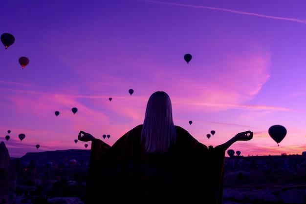 Magische dageraad in goreme cappadocië, turkije. een meisje in een kloof in traditionele kleding omringd door ballonnen in de stralen van de rijzende zon