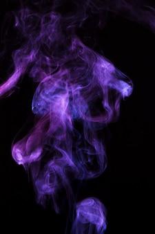 Magische purpere rook die over zwarte achtergrond wordt uitgespreid