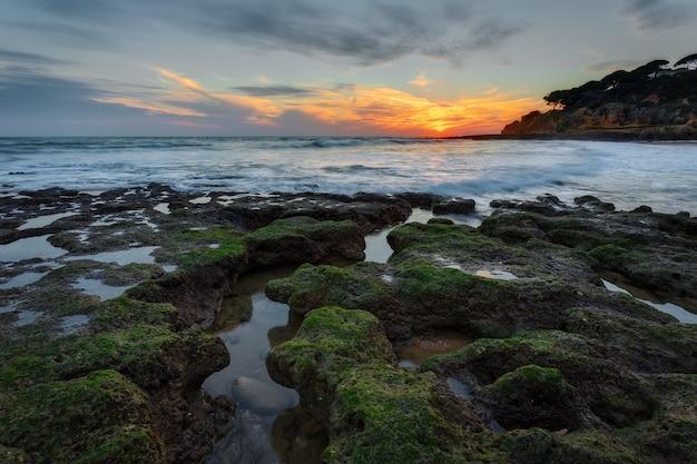 Magische zonsondergang op zee in portugal. stenen mooie vorm op de voorgrond.