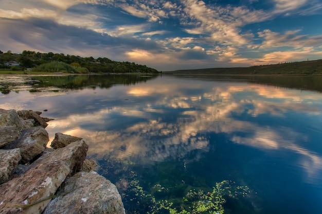 Magische zonsondergang over de rivier. kleurrijke hemel onder zonovergoten weerspiegeld in water.