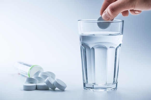 Magnesium pillen en kopje helder water op blauw witte achtergrond.