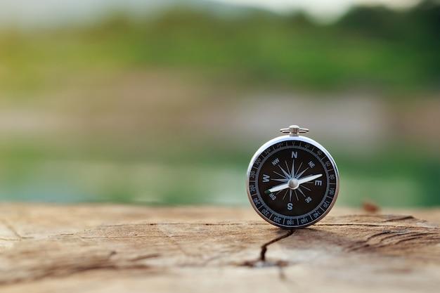 Magnetisch kompas dat rechtop op hout staat met een natuurlijk achtergrondconcept van wereldwijde reizen