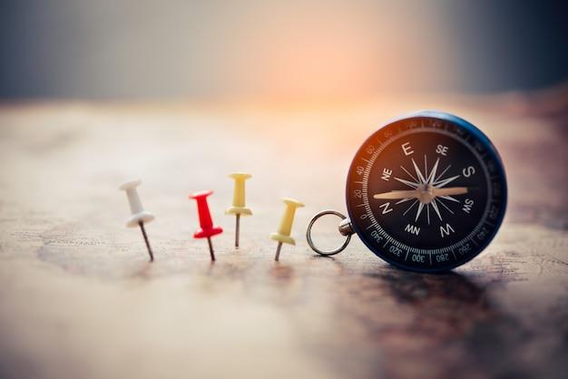 Magnetisch kompas en borduurnaald staat op de kaart. op een wereldkaart conceptueel van wereldwijde reizen