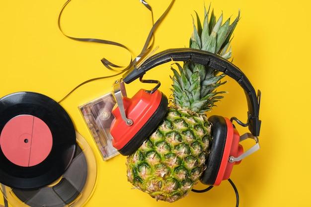 Magnetische audiotape, vinyl en ananas in rode retro koptelefoon op gele achtergrond, bovenaanzicht